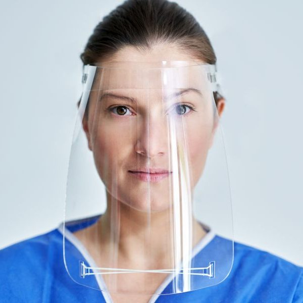 Portrait of female medical doctor or nurse wearing protective face shield